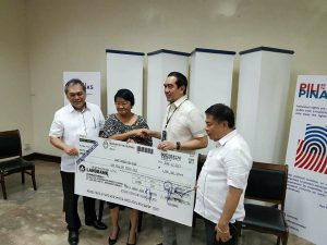 Department of Social Welfare and Development (DSWD) Secretary Judy M. Taguiwalo receives ​the P1 million worth of cash donation from the Commission on Election (Comelec) being handed over by Chairman Juan Andres Bautista (second from right) together with the other officials from the agency.